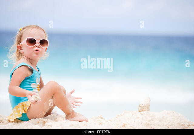 adorable toddler girl playing with sand at the tropical beach - Stock Image