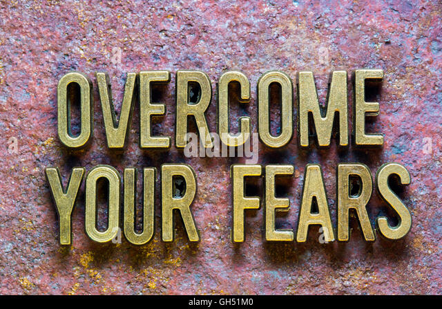 overcome your fears phrase made from metallic letters over rusty metallic background - Stock Image