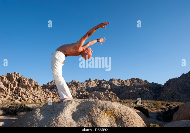 Man in ecstatic yoga back bend outdoors in the desert. - Stock Image