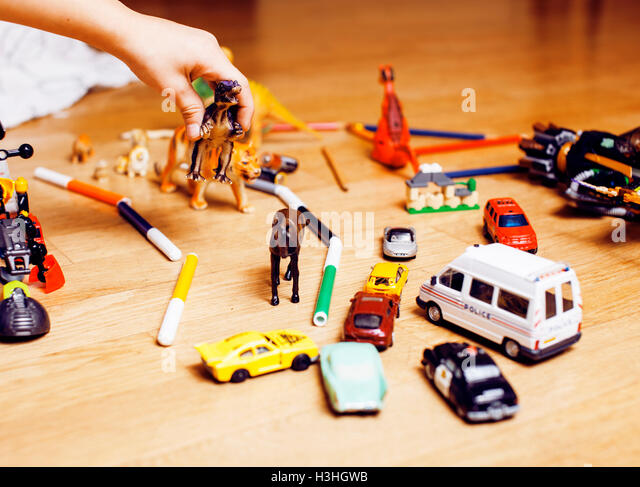children playing toys on floor at home, little hand in mess, free education - Stock Image