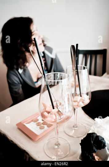 Woman in bar talking, two empty glasses of Sangria foreground, with bill paid next to it, Spain. - Stock Image