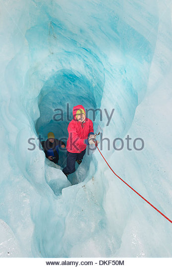 Ice climbers moving up ice cave Fox Glacier, South Island, New Zealand - Stock Image