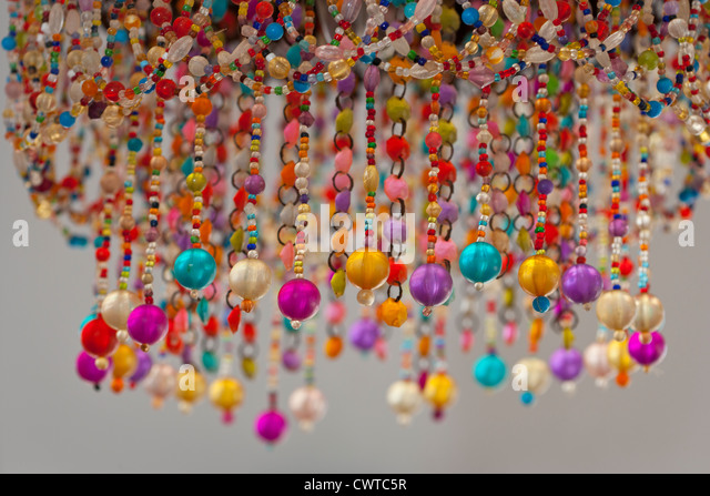 brightly coloured beads as a lampshade - Stock Image