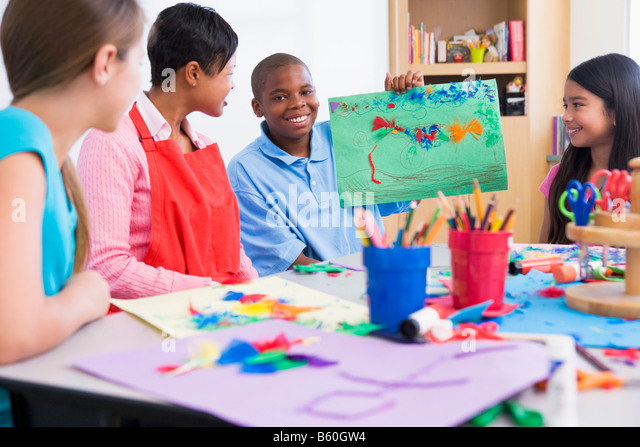 Student showing teacher and classmates his artwork (selective focus) - Stock Image