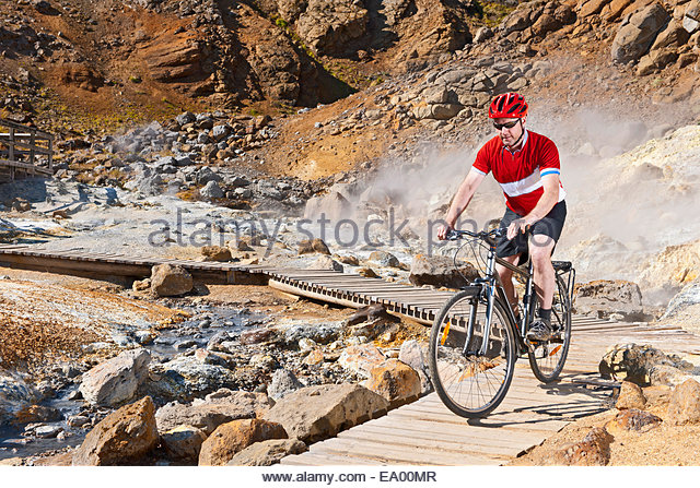 Mature male cyclist riding hybrid bike at geothermal site, Krysuvik, Reykjanes, Iceland - Stock Image