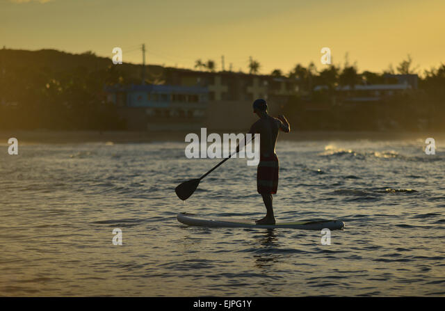 Silhouette of a man on a paddle board during a stunning sunset at Jobos beach. Isabela, Puerto Rico. Caribbean Island. - Stock Image