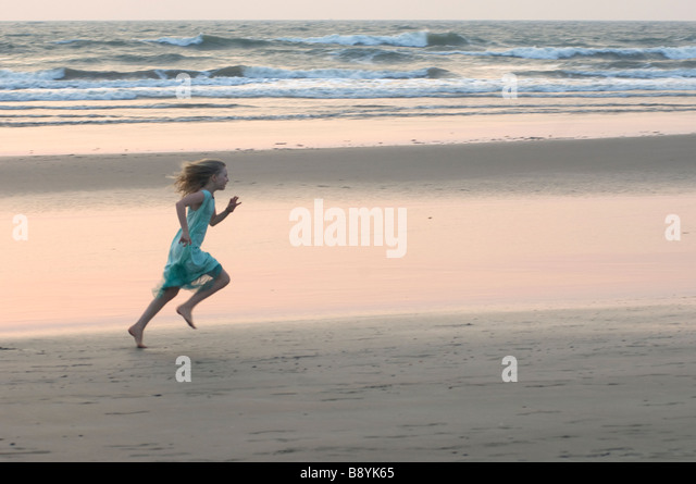 A girl running by the sea Goa India. - Stock-Bilder