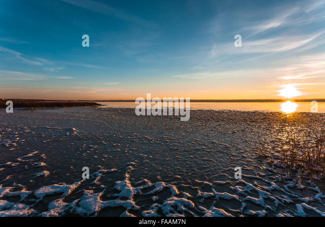 The sun concerns the horizon on the winter coast, being reflected from water and ice. - Stock Image