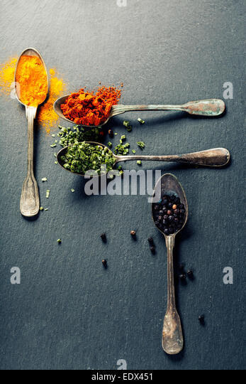 Herbs and spices selection - herbs and spices, old metal spoons and slate background - cooking, healthy eating - Stock Image