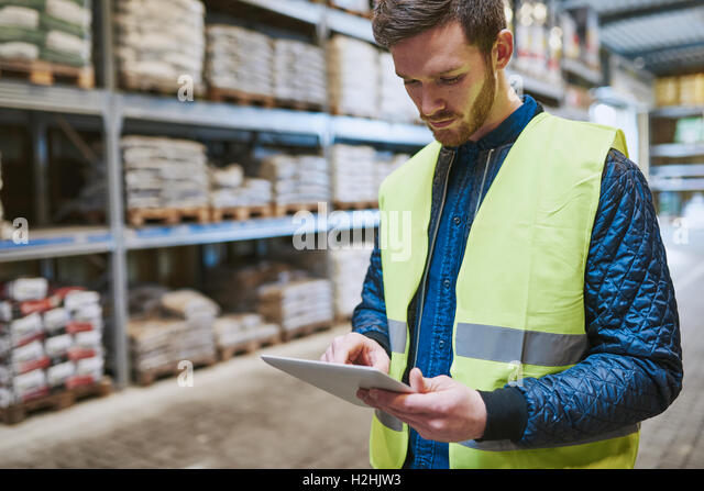 Young man shopping or working in a hardware warehouse standing checking supplies on his tablet with an absorbed - Stock Image