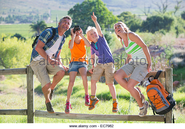 Family resting on a fence in a rural setting - Stock Image