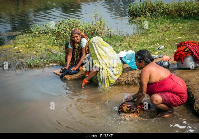 Women washing their clothes on the banks of the Mandakini River in Chitrakoot, (Chitrakut), Madhya Pradesh, India - Stock-Bilder