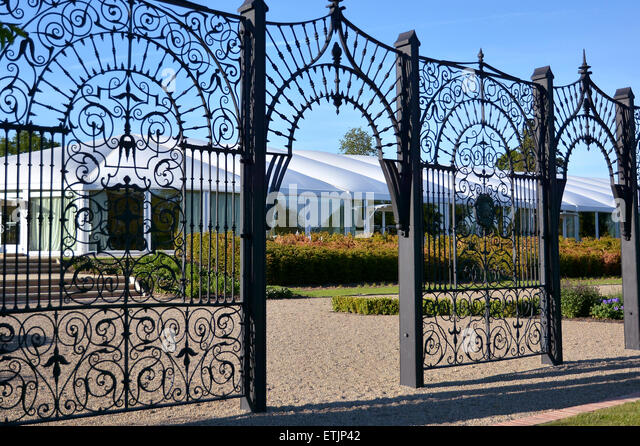 Gates to a English Country Summer Garden with hedges around a gazebo - Stock Image