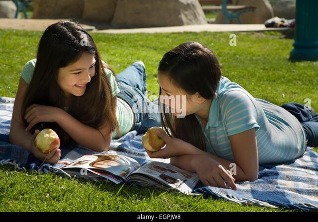Vietnamese/Caucasian and Hispanic/Caucasian girls read together in park. MR  © Myrleen Pearson - Stock-Bilder