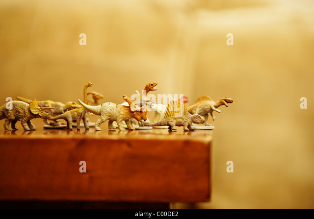 Toy dinosaurs rush off edge of table - Stock Image
