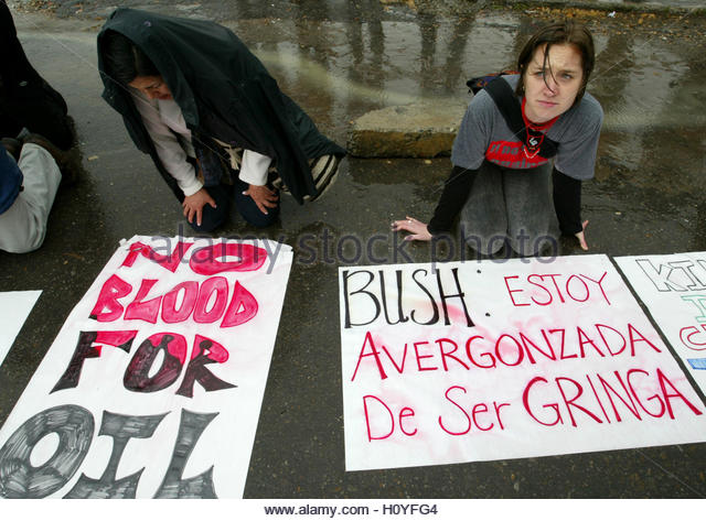 A U.S. citizen (R) with a protest banner that reads: 'Bush, I'm  embarassed to be a 'gringa'' - Stock Image