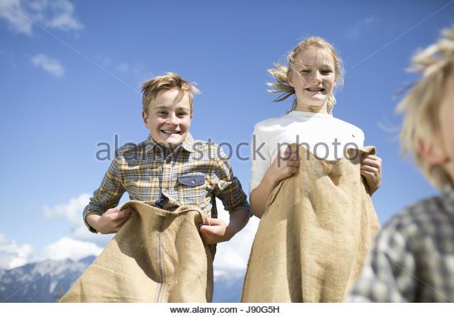 Teenage Children Having Sack Race In Countryside - Stock-Bilder