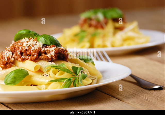 Rigatoni pasta with a tomato beef sauce in the white plate - Stock Image