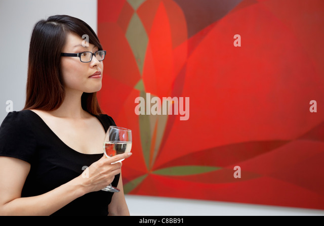 Young woman looking at wall paintings in art gallery - Stock-Bilder