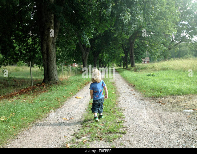 Boy walking along country road, Sweden - Stock Image