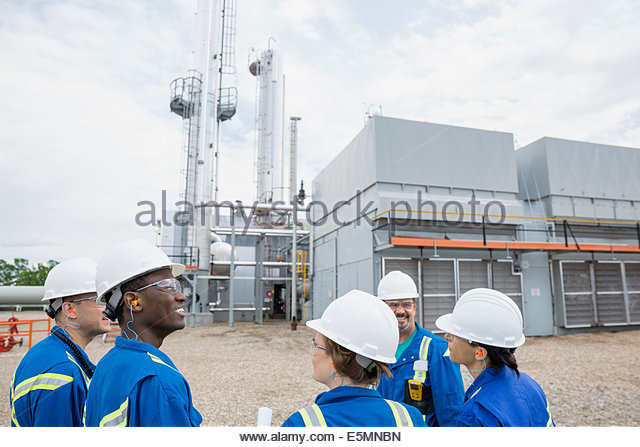 Workers meeting outside gas plant - Stock-Bilder