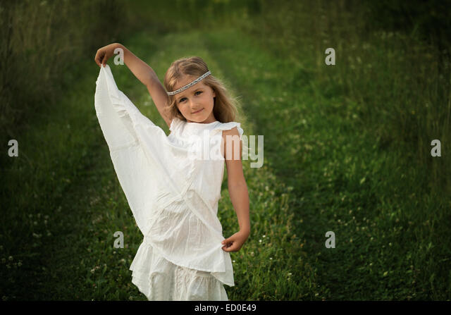 Young girl (4-5) posing in long white dress - Stock Image