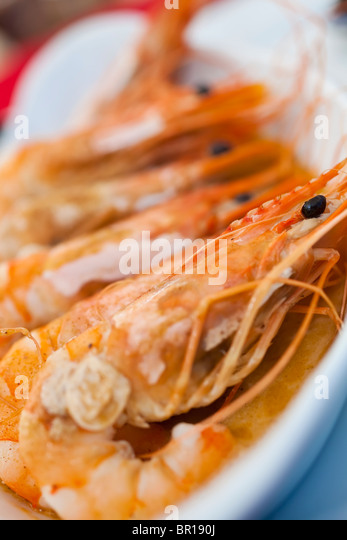 A dish of giant prawns or shrimps cooked in garlic butter, shot on location in a French seafood restaurant in Normandy, - Stock Image