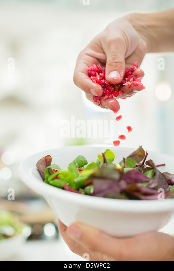 Woman making salad in kitchen - Stock Image