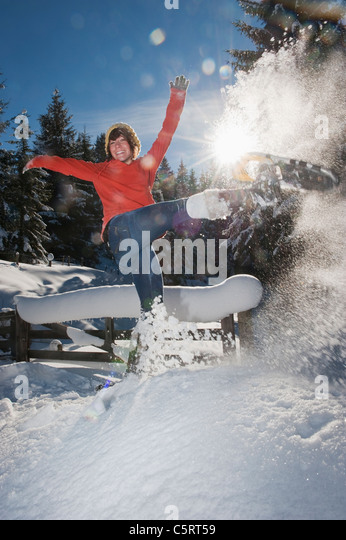 Austria, Salzburg Country, Flachau, Young woman wearing snow shoes jumping in snow - Stock Image