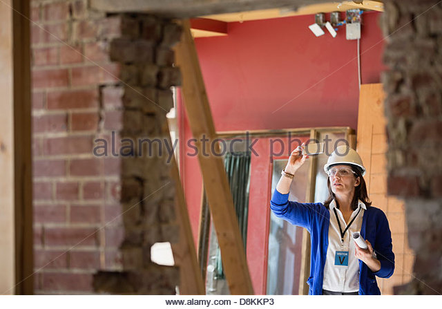Female architect photographing construction site with smartphone - Stock Image
