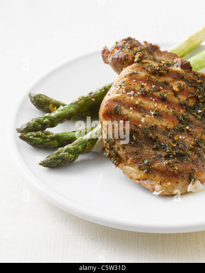 Grilled pork chop and green asparagus on plate - Stock Image