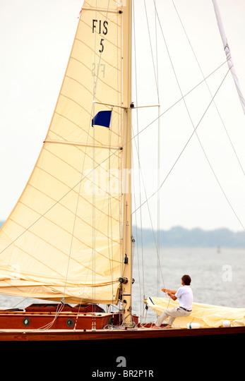 Man pulling sail up on sailboat - Stock Image