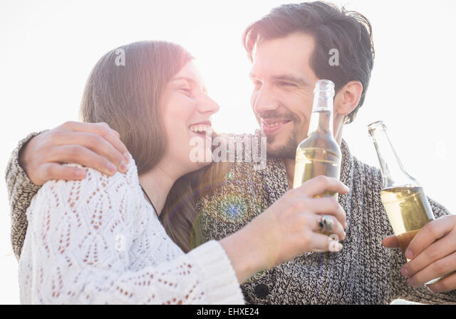 Young couple fun laughing sunset drinking beer - Stock Image