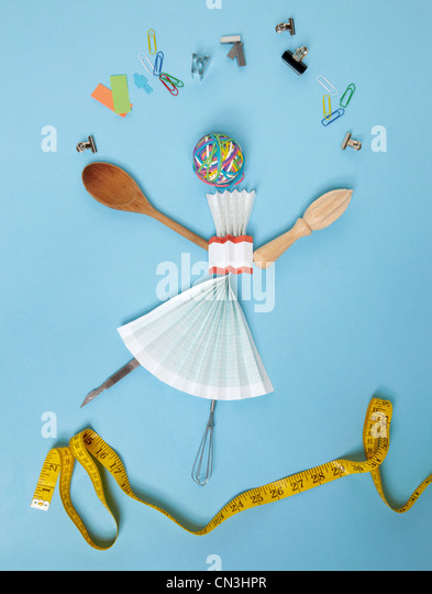 Household objects and stationery arranged against blue background - Stock Image