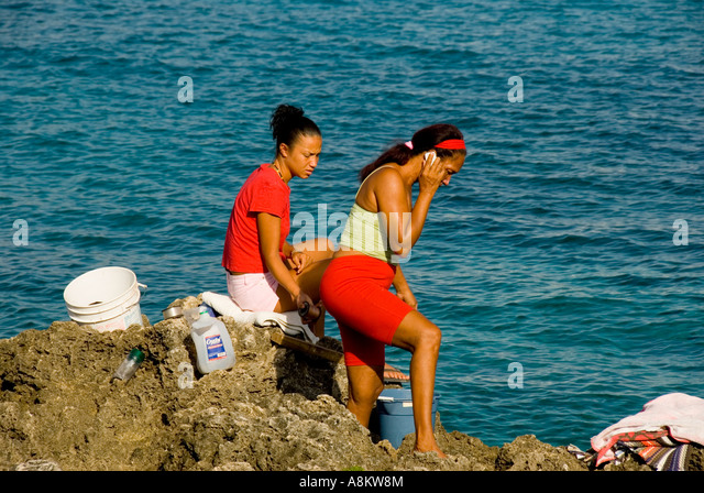 Grand Cayman George Town harbour women fishing cellphone - Stock Image