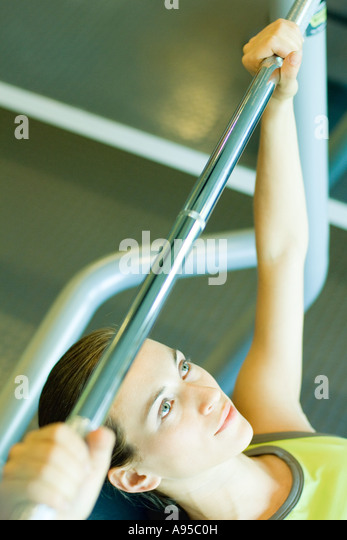 Woman lifting barbell, partial view - Stock Image