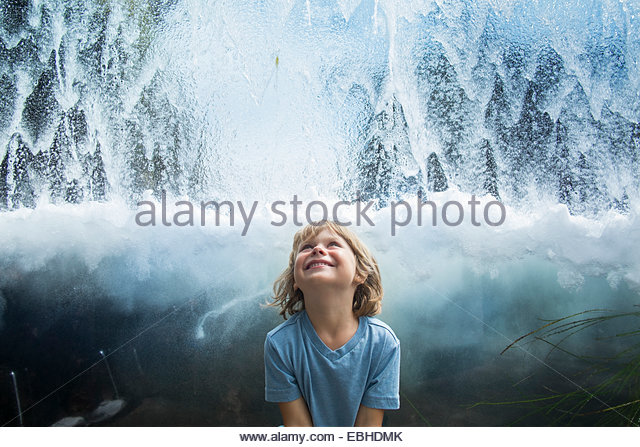 Young boy looking up at flowing water - Stock Image