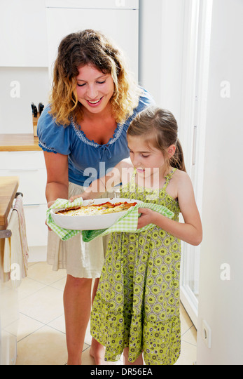 Girl Carrying Baking Dish - Stock-Bilder