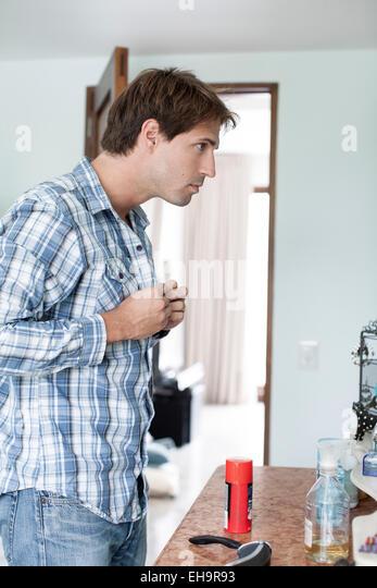 Man buttoning shirt - Stock-Bilder