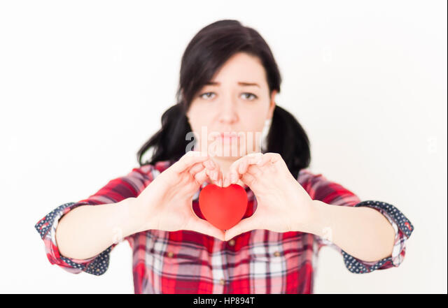 Sad young girl holding a small red heart and her fingers in the form of heart. Unrequited love concept, blurred - Stock Image