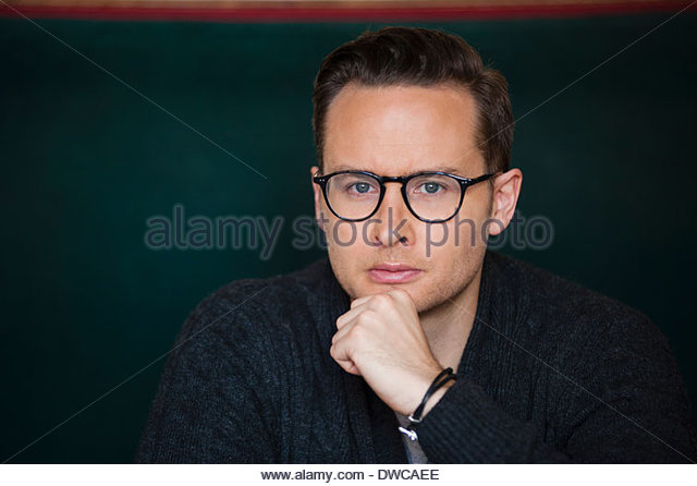 Close up portrait of thoughtful mid adult man - Stock Image