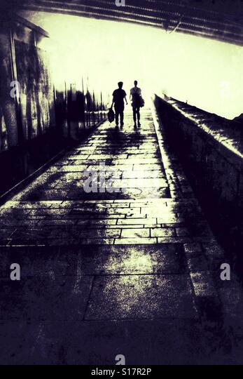 Two silhouetted people walking along an urban pathway. - Stock-Bilder