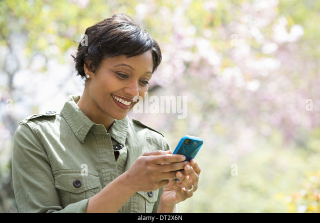 Sunshine and cherry blossom A woman checking her smart phone - Stock Image