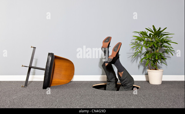 Business man disappearing through hole in the floor - Stock Image