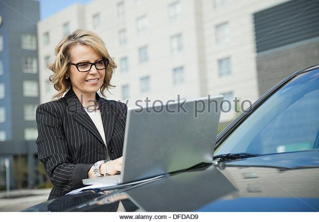 Businesswoman using laptop on car hood outdoors - Stock Image