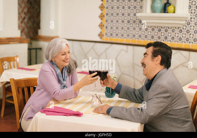 Older couple toasting with wine in restaurant - Stock Image