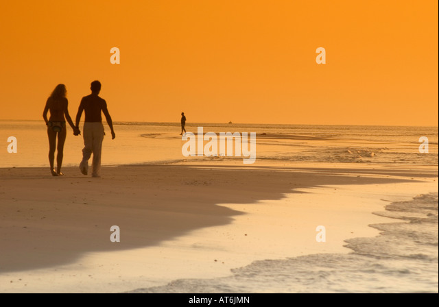Couple on the beach, silhouetted at sunset, Maldives - Stock Image