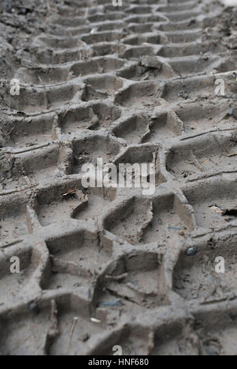 Close up shot of tyre tracks / tire marks in soft mud at winter time. - Stock Image