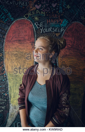 Portrait smiling,pensive Caucasian tween blonde girl against wall with chalk wings - Stock Image