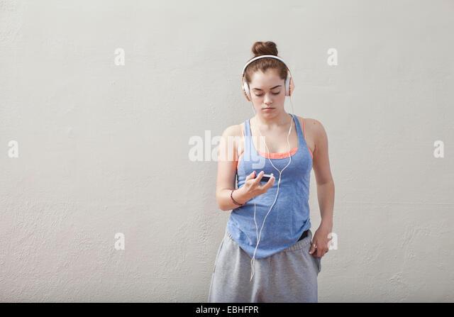 Teenage girl listening to smartphone music in ballet school - Stock Image